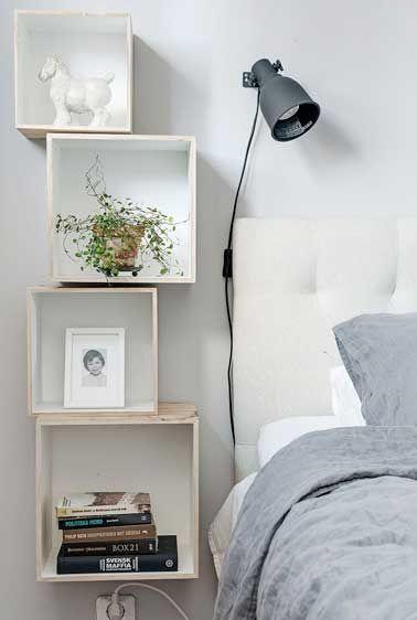 quatre caisses en bois blanchis sont fixees les unes au dessus des autres pour former un ensemble table de chevet et etageres murales