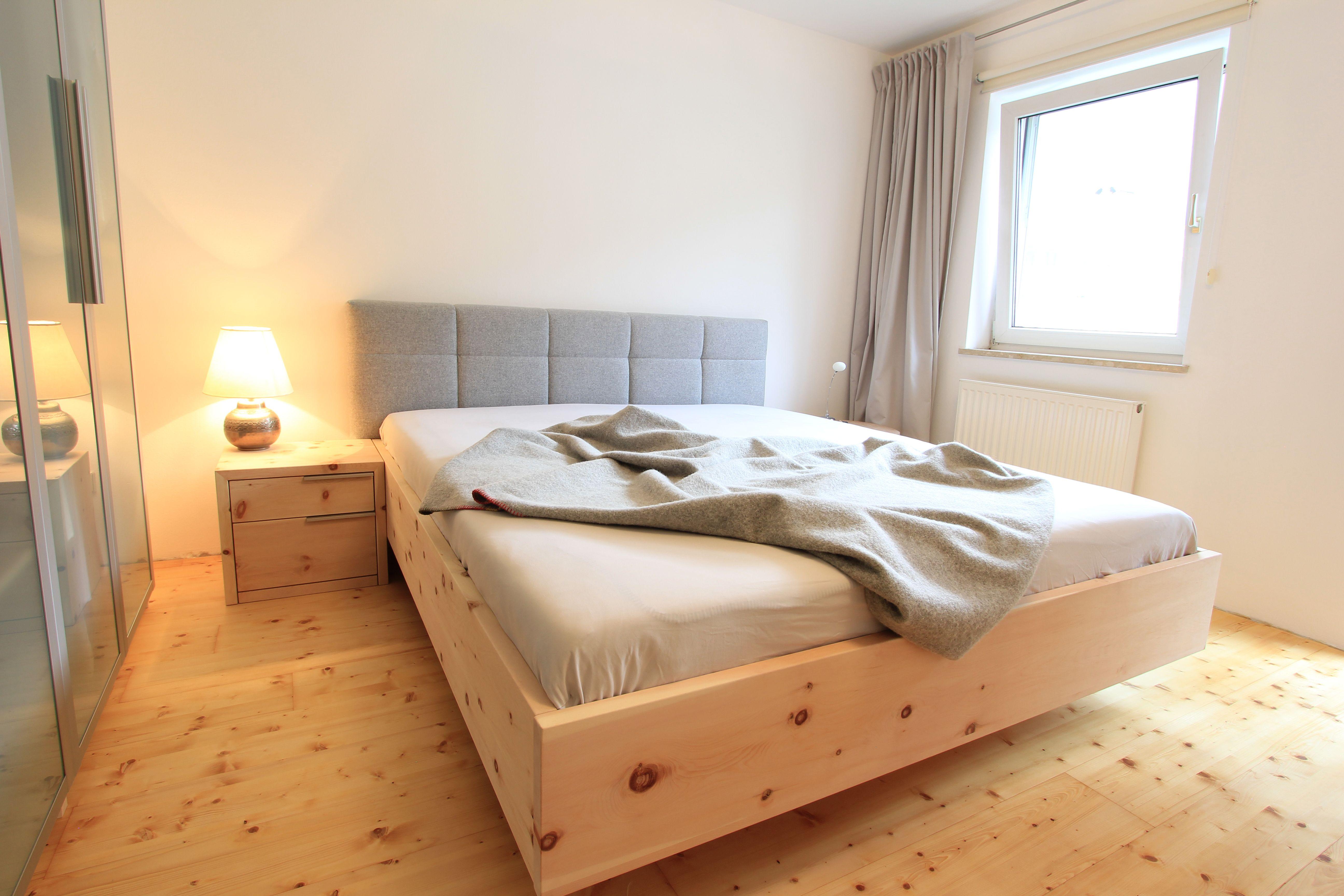 zirbenbett aus unserer tischlerei mit kopfhaupt aus hellem lodenstoff bett in schwebeoptik. Black Bedroom Furniture Sets. Home Design Ideas
