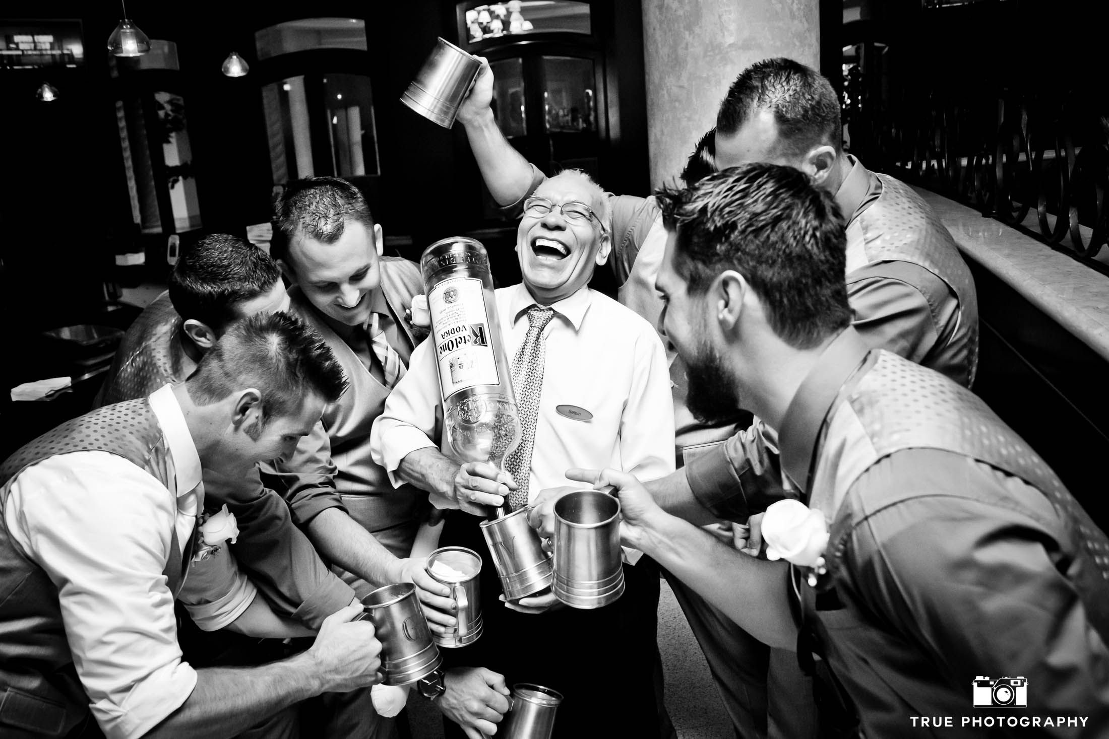 Funny Candid Moment Of Groomsmen With Dad Drinking Big Bottle Liquor At Wedding Reception