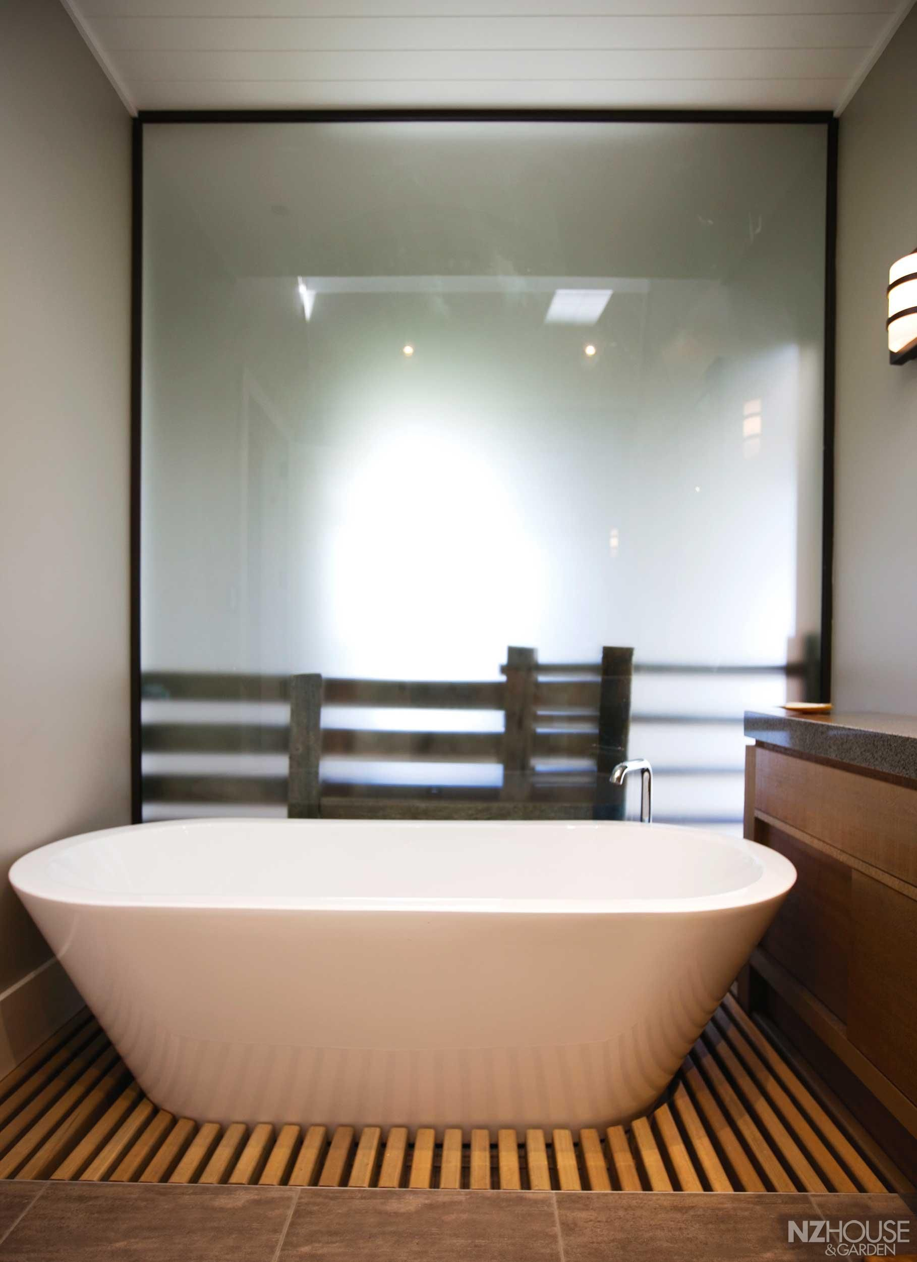 Kauri duckboarding around a freestanding bath in the main bathroom