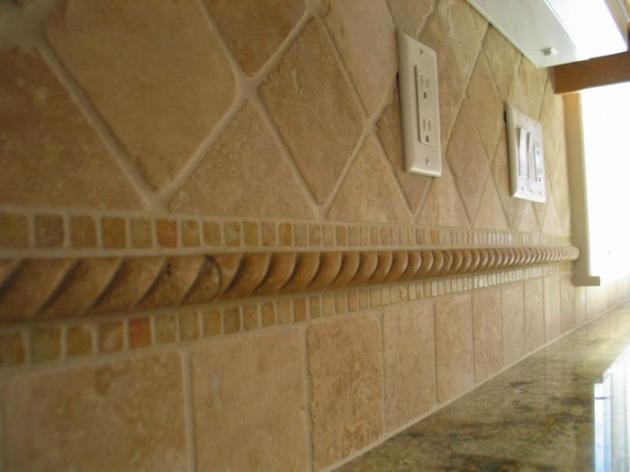 This backsplash, of Imperial travertine, features tumbled 4x4 inch tiles in both a ...