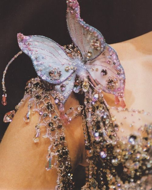 1. buy fake butterflies from Michael's 2 adorn with pretty beads 3. attach to dress