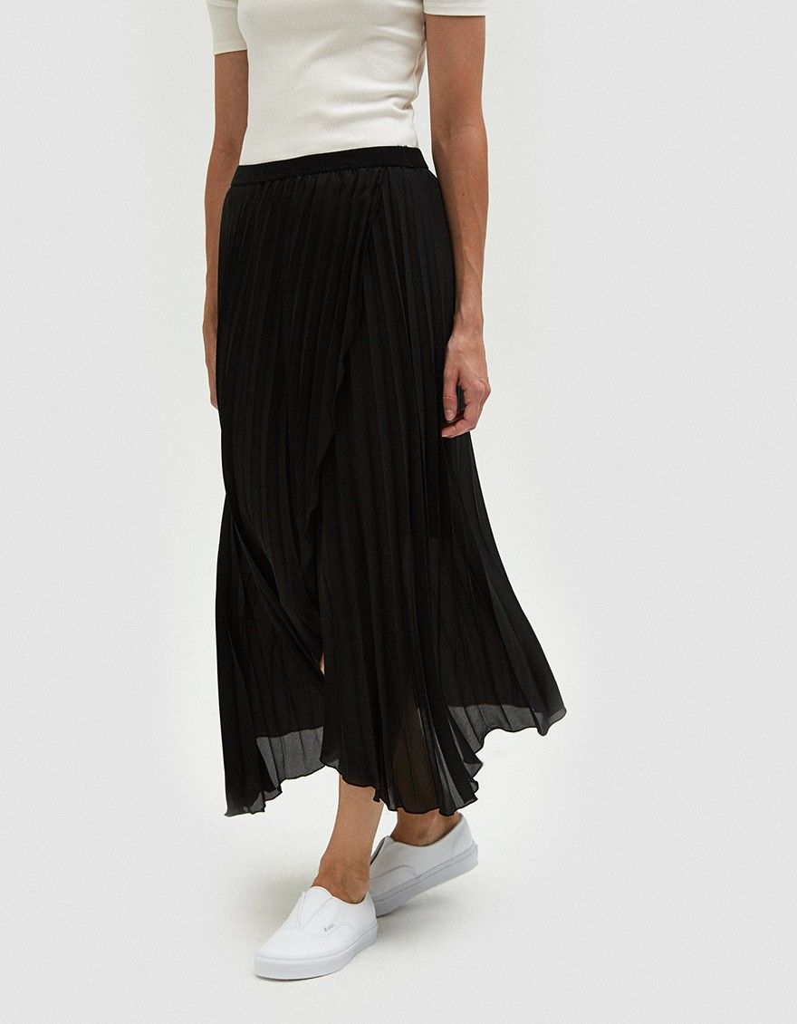 7308f6de01 Lightweight skirt from Farrow in Black. Semi-sheer fabric. Allover accordion  pleats. Mid rise. Concealed side zip closure. Wrap-look front.