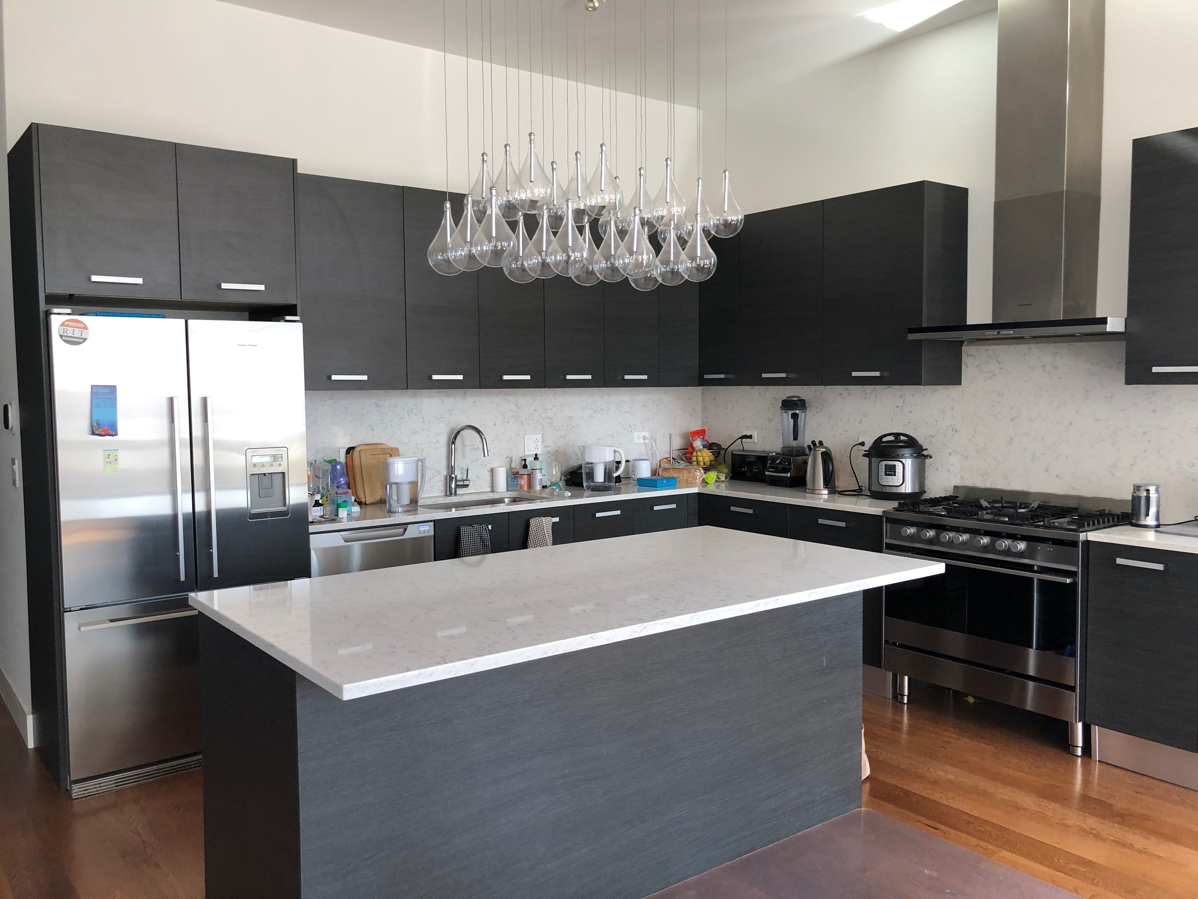 Modern Kitchen With Espresso Cabinets Bulb Chandelier Stainless Steel Appliances Silver Hardwa Open Kitchen Layouts Kitchen Layout Espresso Kitchen Cabinets