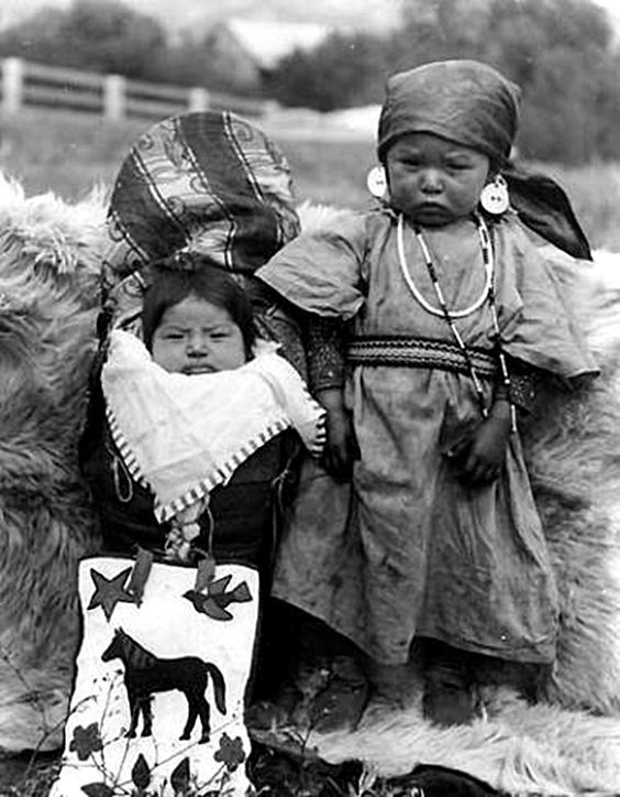 An Colville infant and young girl pose outside on fur skin. The infant is in a blanketed cradleboard, wears a bib with striped edging. A beaded bag with a horse, bird star and flowers is propped up in front of the cradleboard. The young girl wears a kerchief, earrings, necklaces, moccasins, and a woven belt over her dress, ca. 1900-1910 .: