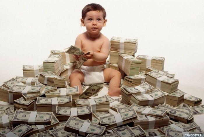 Ребёнок играется в огромной куче из пачек денег ...