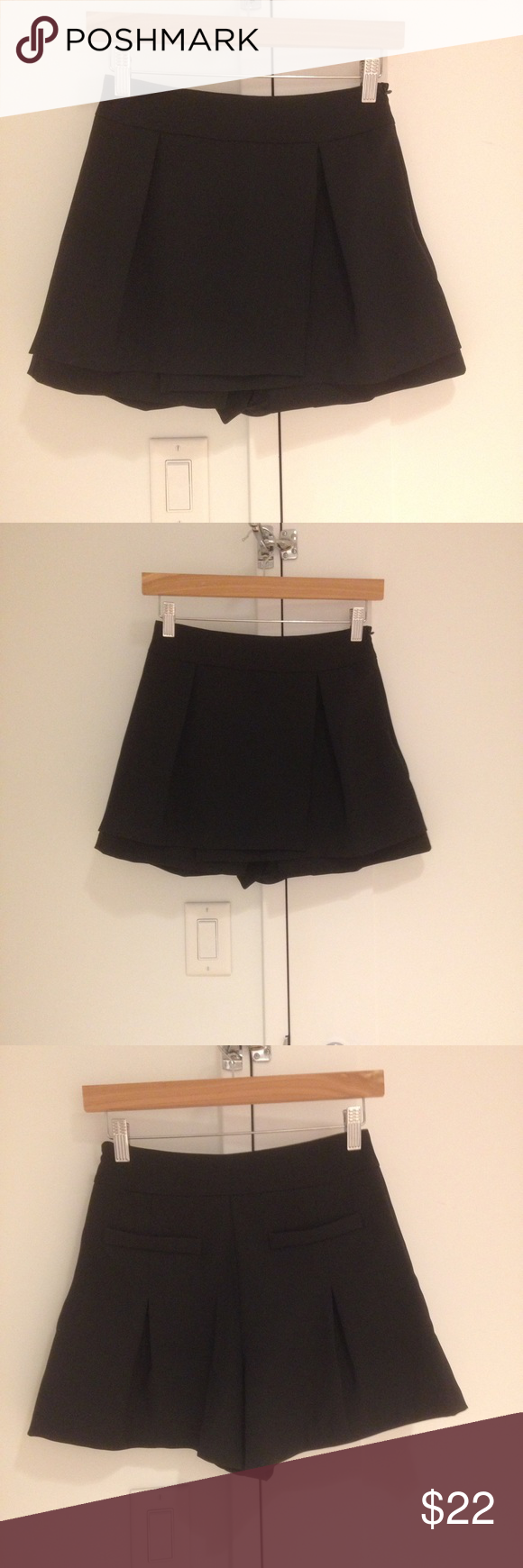Black mini skort with front pleats Side zip. 100% polyester. Please note that this is a skort (not a skirt). Shorts Skorts