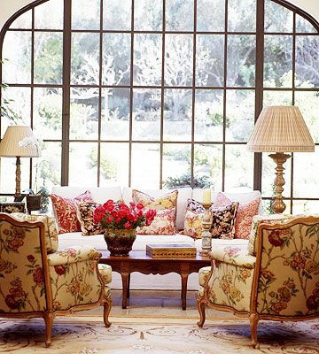 Sitting room arrangement in front of large window.  Consider for the basement garden room.   The living room includes a custom-designed coffee table and sofa as well as a few French antiques and a 1930s needlepoint rug.