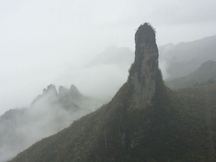 A spire of limestone rising through fog and mist in China