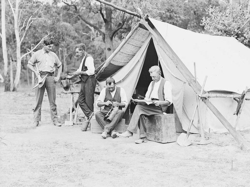 Miners relax in front of their tent on the site of the Newport gold discovery & Miners relax in front of their tent on the site of the Newport ...