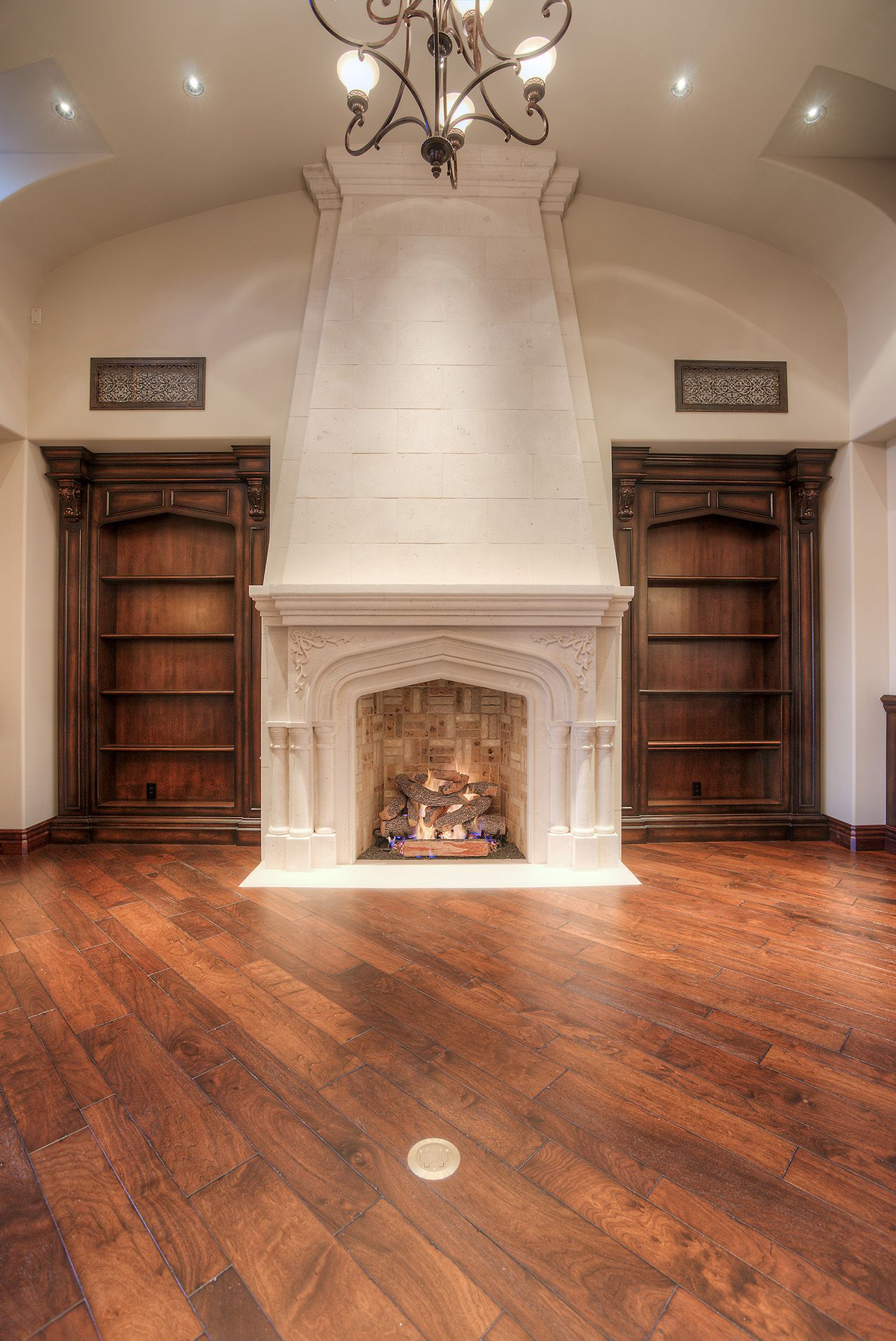Elegant stone fireplace with built in wood book shelves on both