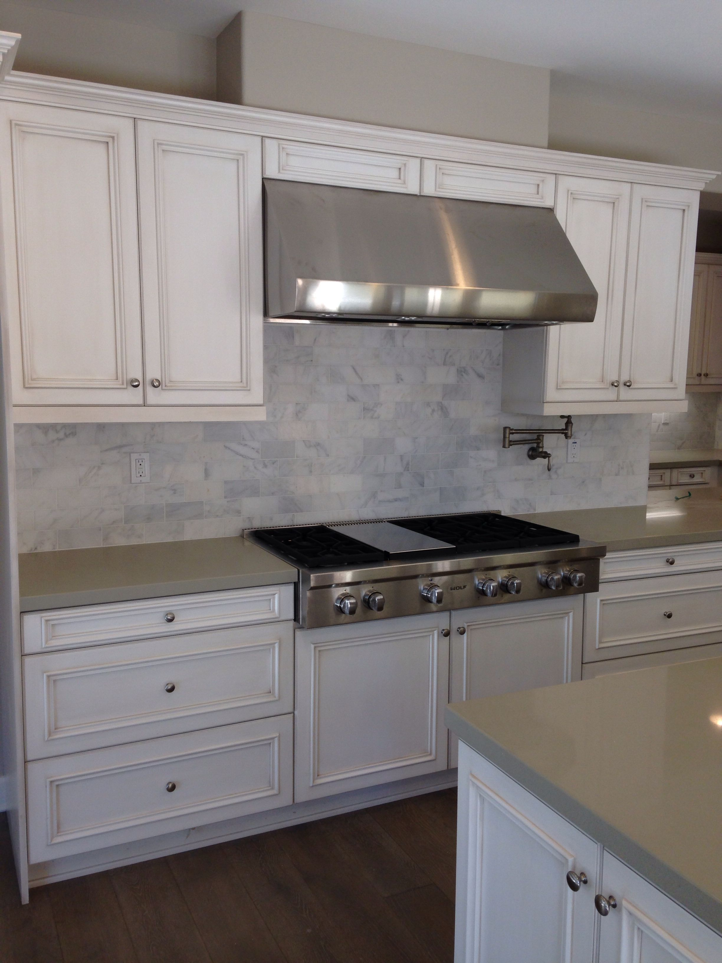 Kitchen With Antique White Glazed Cabinets Cinder Caesarstone 3x6 Offset Calcutta Tile Splash