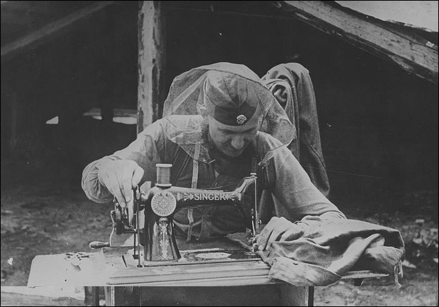waffen-SS protected by a mosquito net did some sewing. (1942, Russia)