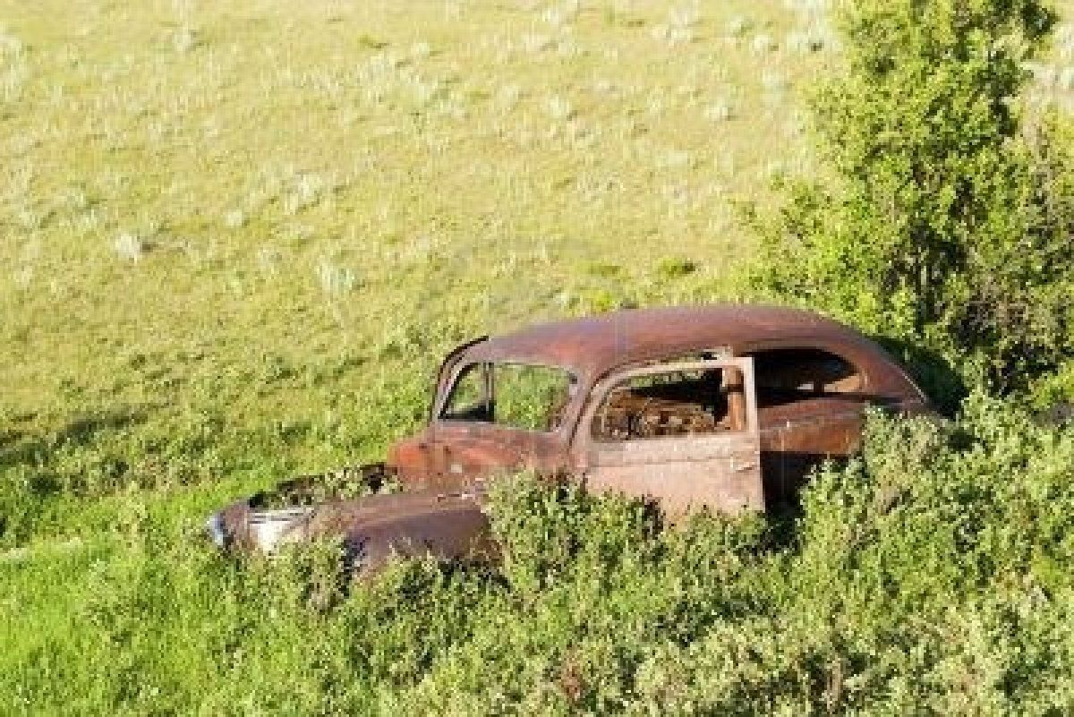 An old car sitting on the prairie forgotten and overgrown with ...