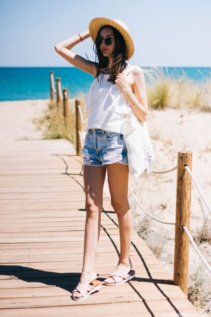 Fashion Blogger On Beach Wearing Straw Hat And Ripped Jeans Girl Sitting On The Sand With Bare ...