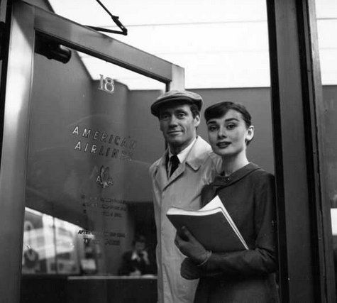 """The actress Audrey Hepburn photographed with her husband Mel Ferrer (actor, dialogue coach and film director) by Milton H. Greene in the agency of American Airlines at the Ciampino Airport in Rome (Italy), before leaving for Los Angeles, California (USA), after the end of filming their new movie """"War and Peace"""", on October 26, 1955."""