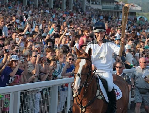 """""""Bearing the Olympic torch  Zara Phillips, former world equestrian champion and daughter of Princess Anne, carries the Olympic torch atop her horse Toytown to the Cheltenham Racecourse on May 23 in Cheltenham, England. After arriving in the U.K. on May 18, the flame is embarking on a 8,000-mile relay involving 8,000 torchbearers leading up to the opening ceremony of the Olympic Games."""""""