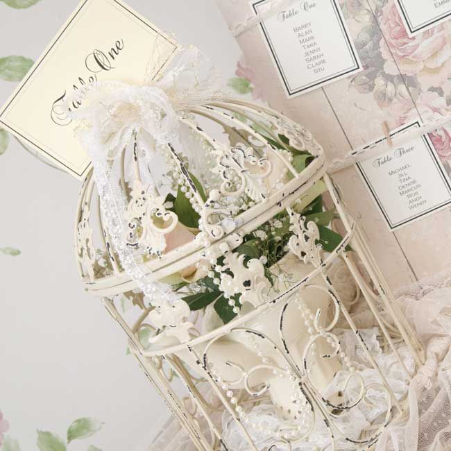Beautiful birdcages to hire These distressed white birdcages would look perfect as part of a vintage country garden theme. Use them as table centres, with the table name tied to the top with a piece of ribbon as shown here. Fill them with hydrangea heads for a country look or drape over pearls and lace for a 20s-inspired look