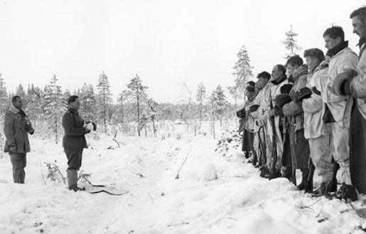 Finnish Army Lieutenant Aarne Juutilainen and his company holding a Christmas service near the Kollaa River, Finland, 24 Dec 1939.