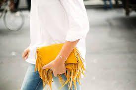 ¡Accesoriza! Puedes usar la aplicación de flecos en bolsas de mano en colores radiantes como este mostaza para un look casual