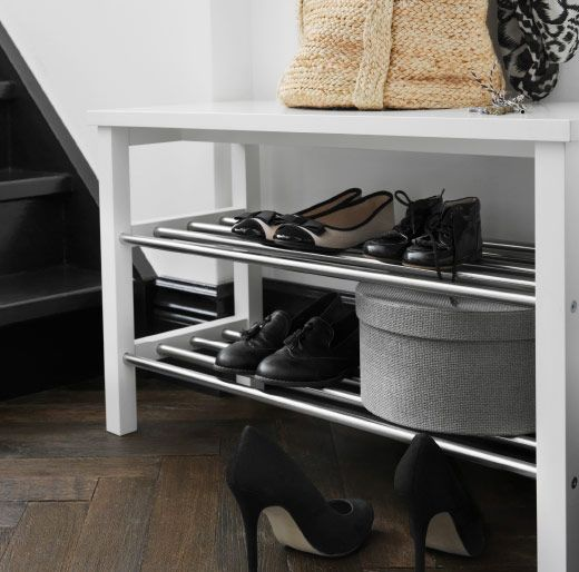 Close-up of a white bench with shoe storage filled with shoes and a ...