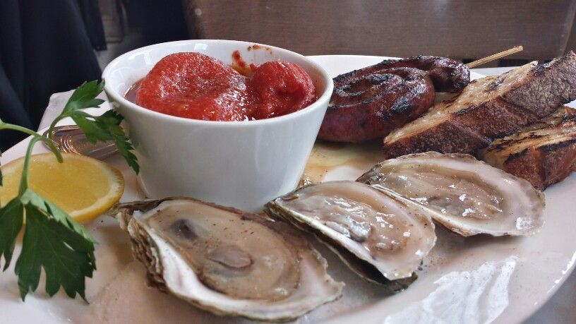 Grilled handmade lamb sausage, oysters and braised tomato with crisp bread.