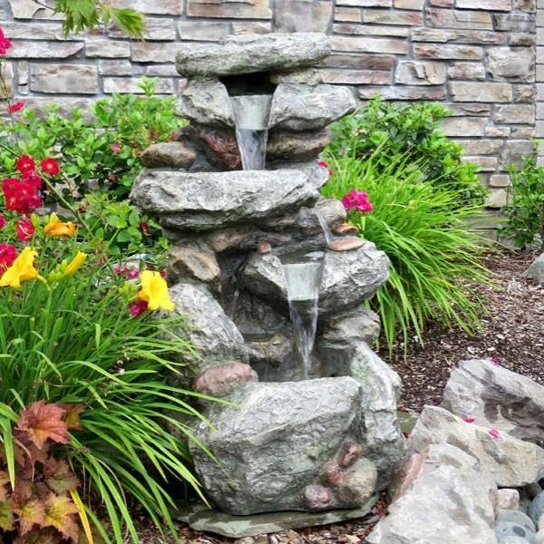 wasserbrunnen im hinterhof-naturstein mit pflanzen-bewachsen - naturlicher bachlauf garten