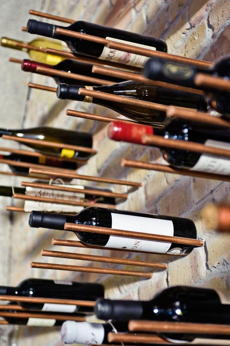 Koperen pennen in een muur van schoon metselwerk zorgen voor een speels wijnrek.