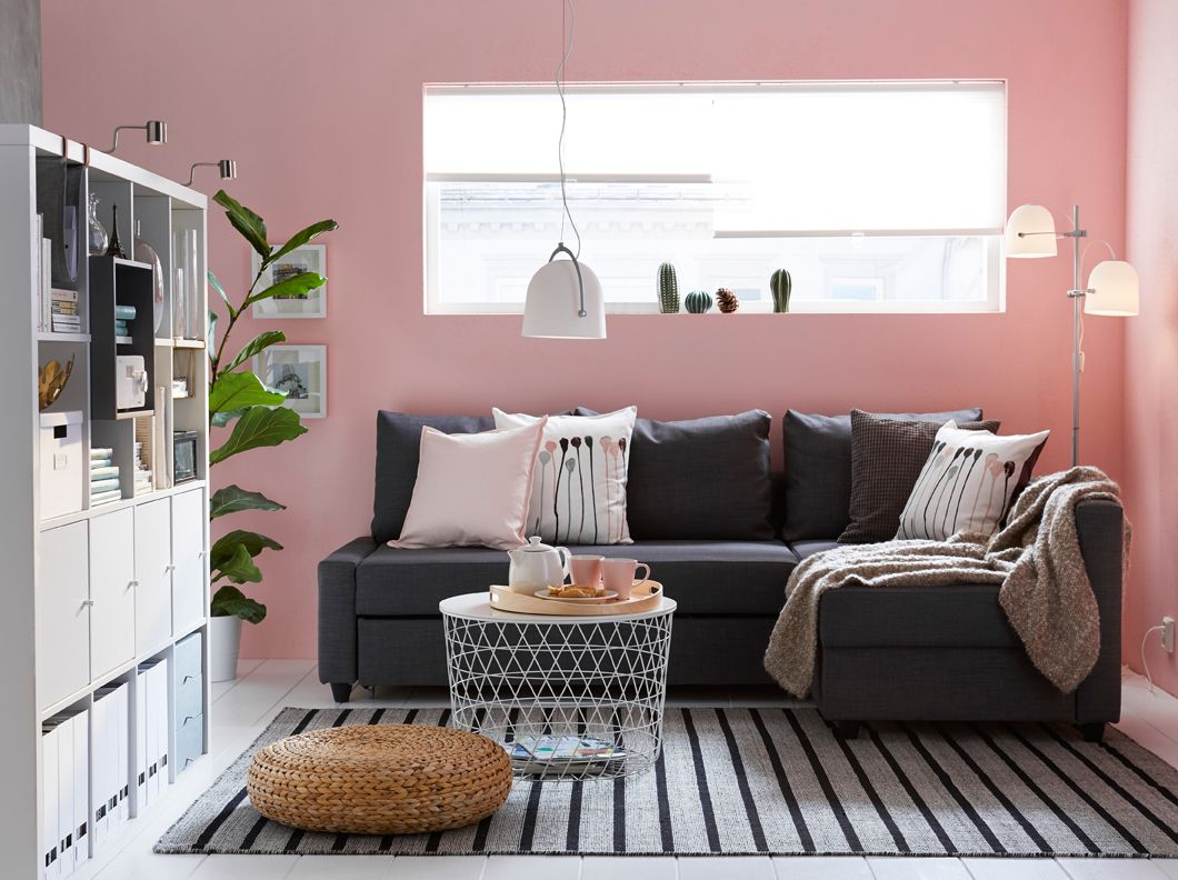 Living Room With Dark Gray Sofa Bed Pink Walls And A Striped Rug