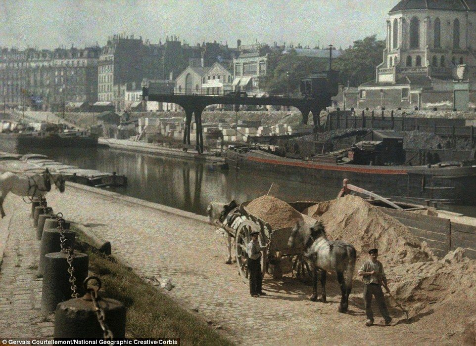 Workers with horses and carts carrying supplies alongside the river