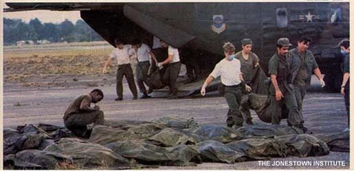 """Military members carry the bodies of Jonestown victims from a helicopter. """