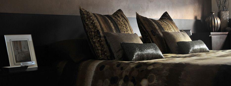 Toques de color intenso para dormitorio principal. Cojines anaranjados,cobres y marrones chocolate, lo complementan.