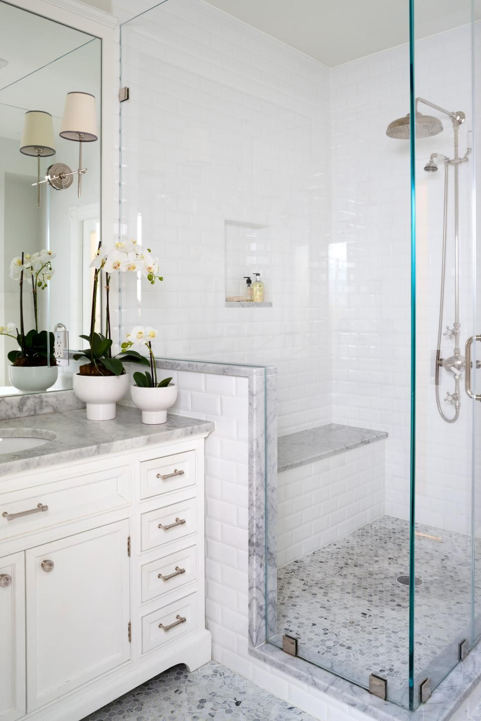 pictures to hang in master bathroom%0A A glassenclosed shower is fitted with a bench is this traditional master  bathroom space