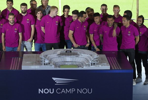 Barcelona's players pose in front of a mockup of the New Camp Nou during the presentation of FC Barcelona stadium's remodelling project, at the at the Camp Nou stadium in Barcelona, on April 21, 2016.