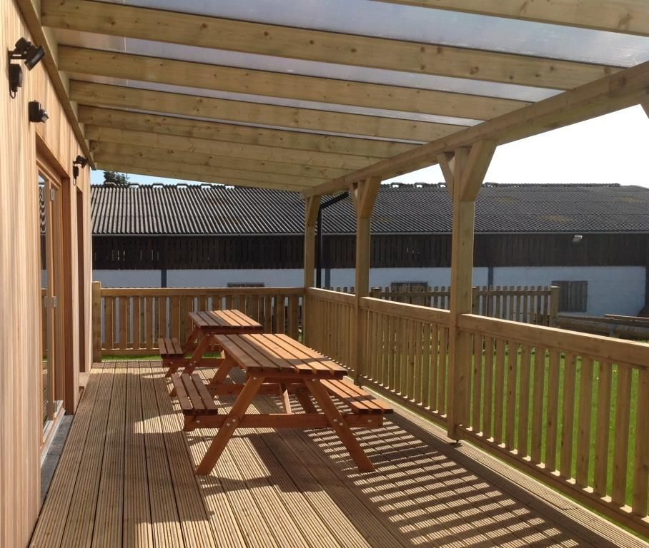 A Timber Veranda With Polycarbonate Roofing Lets Light