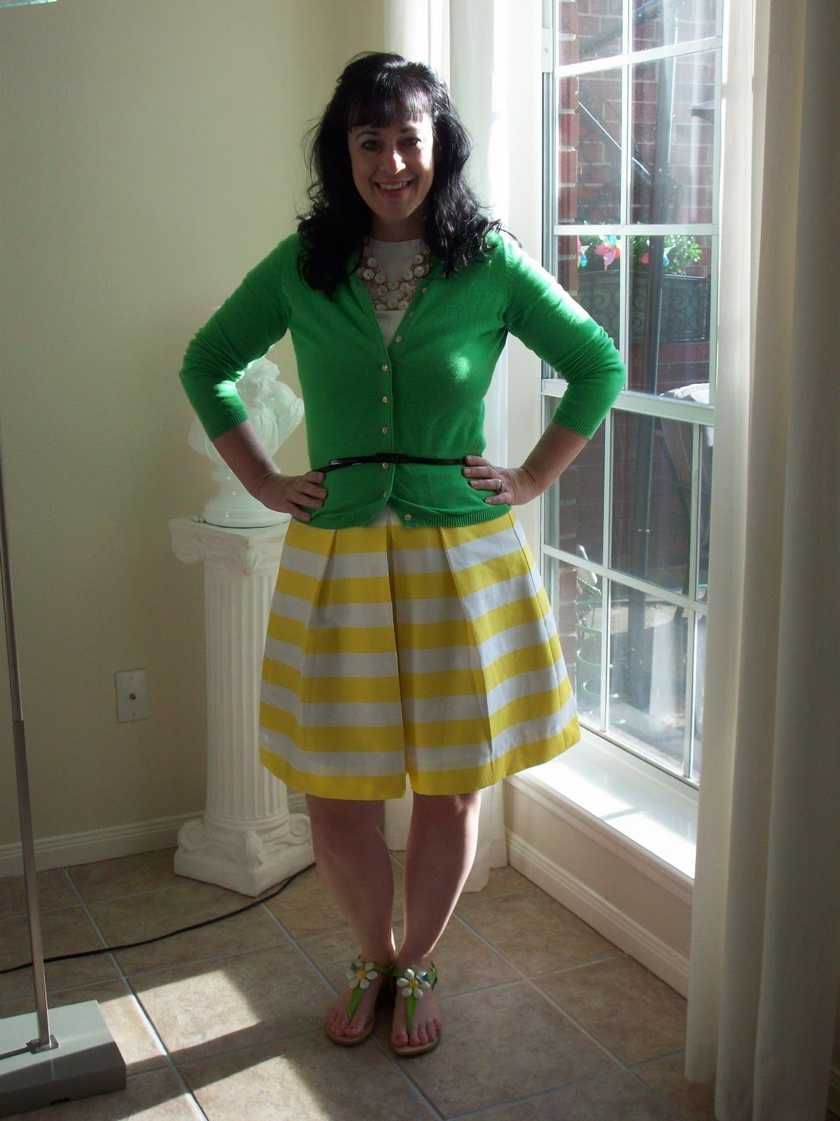 Kelly green cardigan with a lemon yellow printed skirt.