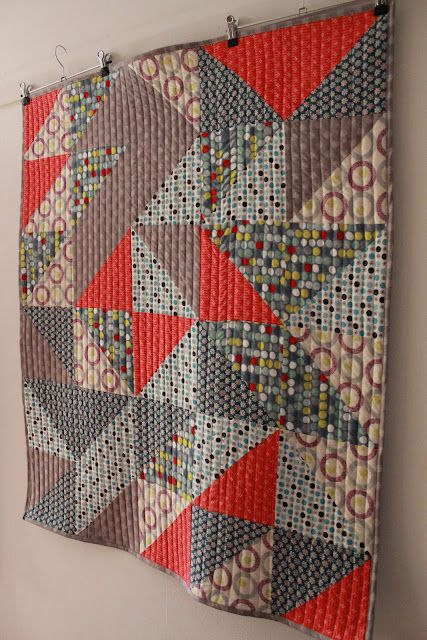 like the half square triangles arranged to make larger shapes and the straight line quilting