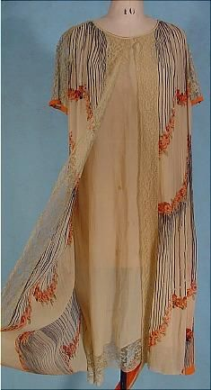 c. 1926 Deco Tea-colored and Orange Design Crepe Day Dress.Tea colored thin silk crepe fabric in two layers. The under sheath which you see in the front panel, hemmed with wide lace, and then the attached overdress, pleated from the shoulders, edged in wide ecru lace which is totally open front and back and only ties down with the separate original tie belt. The design is a print in the silk fabric. Black stripes ending in orange flowers in the deco design. Front