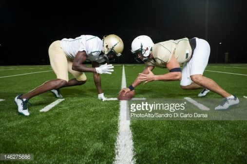 Stock Photo : Opposing football players crouched at line of scrimmage