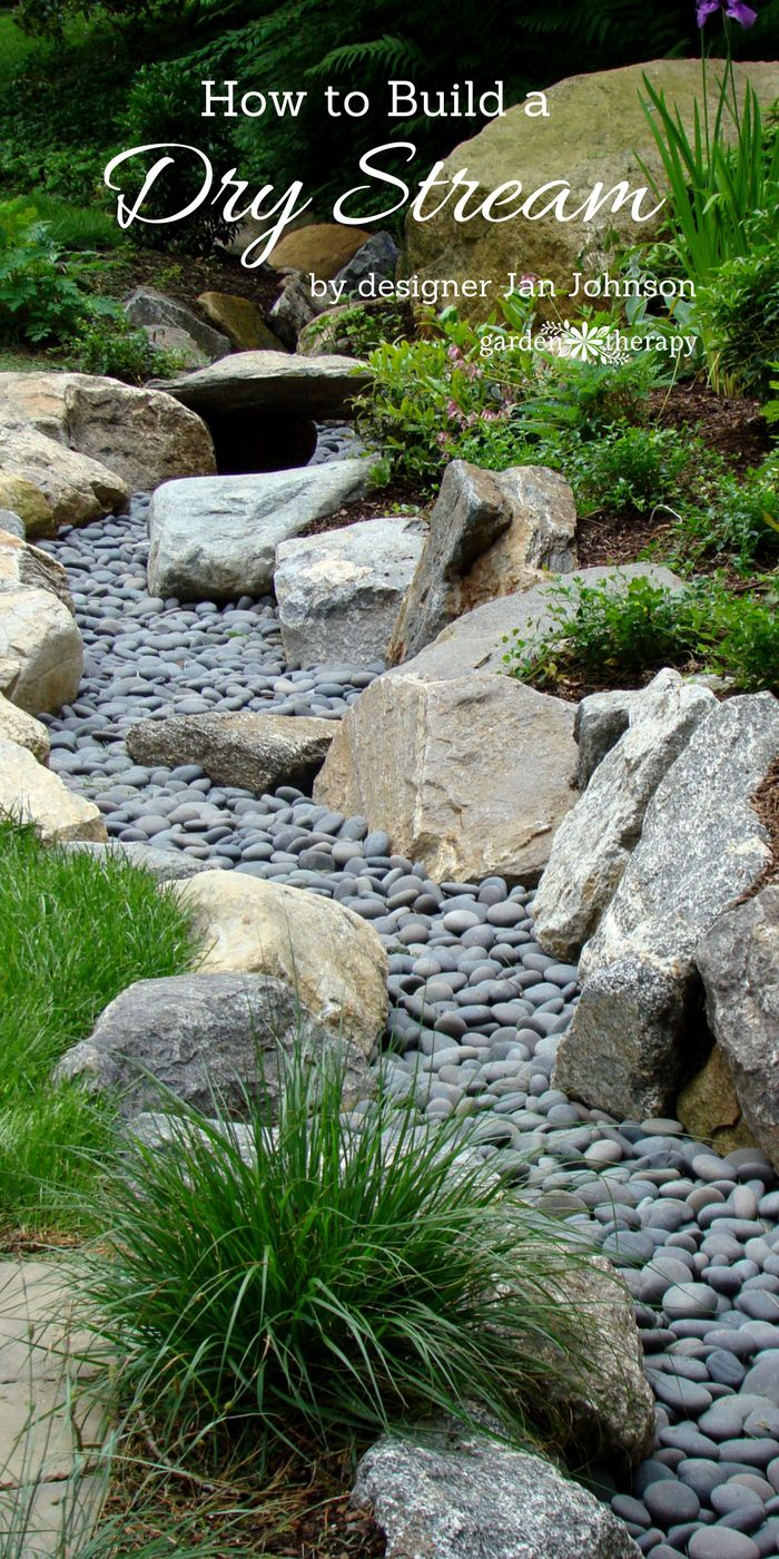 Dry creek against lawn boardered by larger