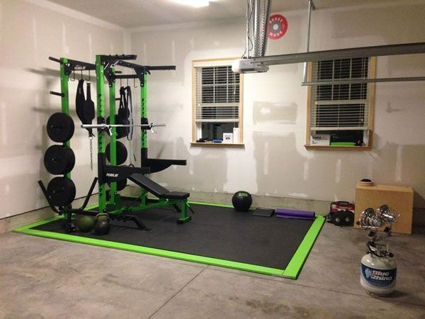 Simple and clean heated garage gym with green weight bench
