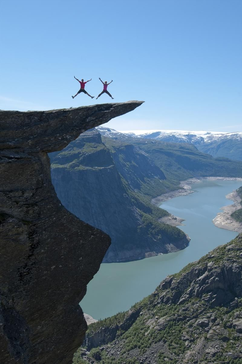 Trolltunga, Hardangerfjord region in Norway. 10 hours hard hike to get there and back - bring hiking boots and be equipped for the high mountains. Trolltunga is about 1,100 meters (3,500 feet) above sea level and about 700 meters above the lake down in the valley. Folgefonna National Park and the glaciers in the background. Travel: Go to Bergen (BGO) - then a 3 hours drive to Odda. You can also climb to Trolltunga on a via ferrata with a guide from opplevodda.com. Photo by Stig Tronvold.