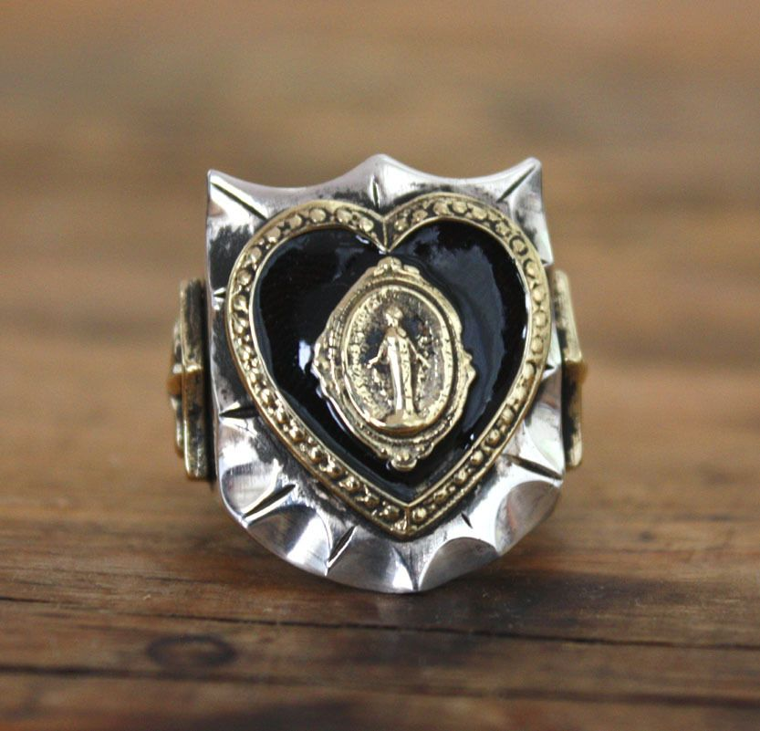 (MARY HEART) is cast in solid sterling silver with brass accents. And I also offer them in the original melted peso style of the 40's thats white alloy/brass. Please make size choice when you checkout