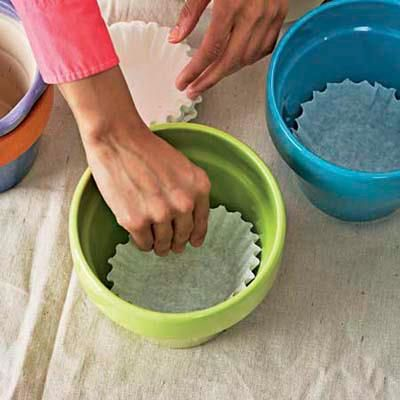 Line flower pots with coffee filters to prevent dirt falling through the hole in the bottom of the pot
