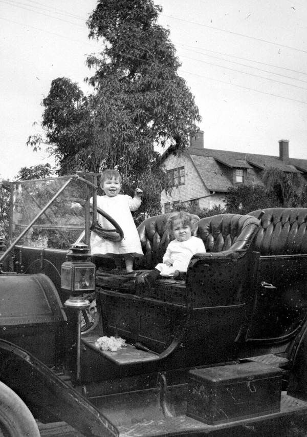Children in a Rambler in front of their home