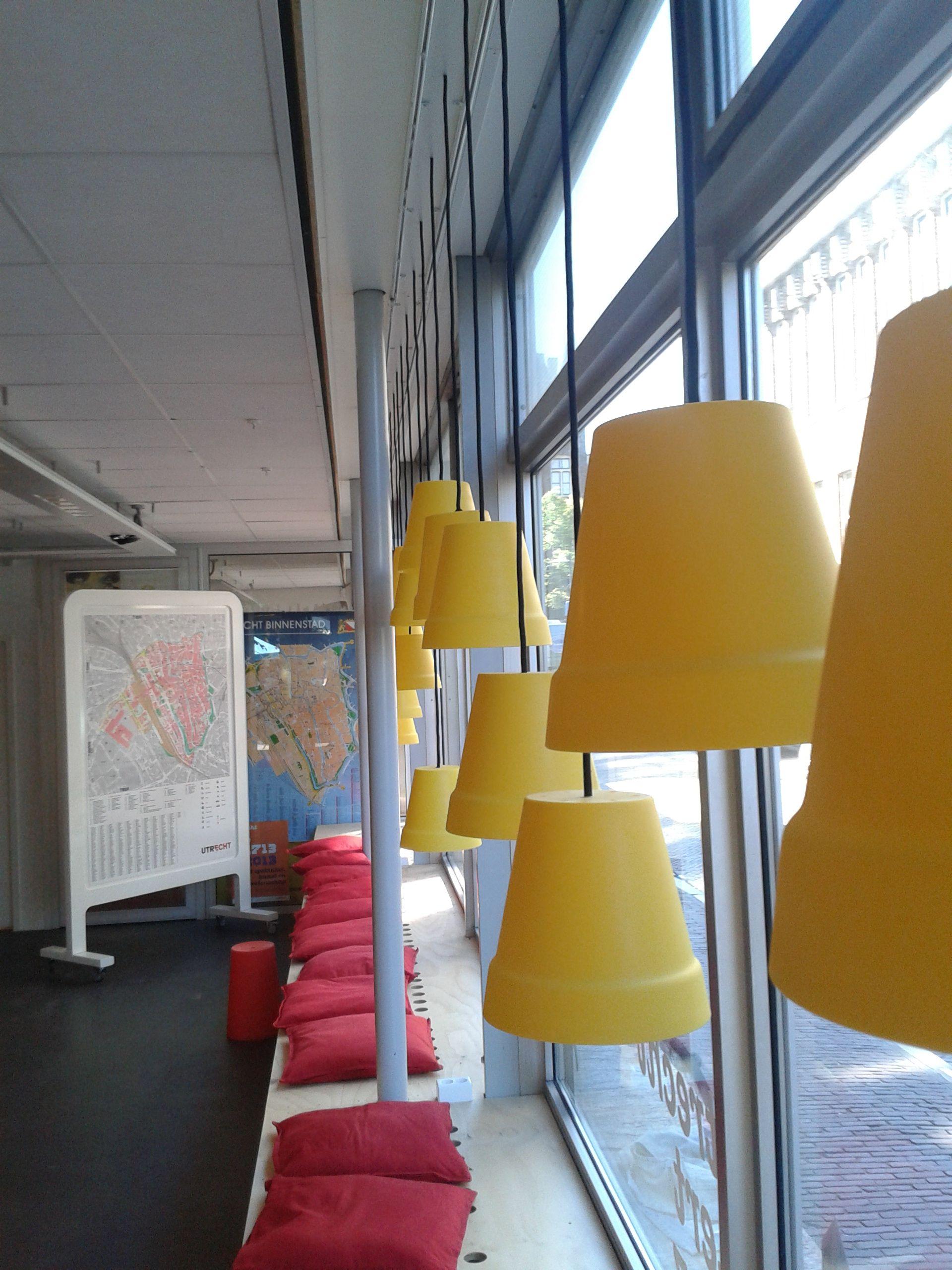 Er zijn verschillende zitplaatsen  voor gasten . Op deze foto zie je een vensterbank met kussens waarop een gast op kan zitten. Er hangen ook lichten bij de raam. Ze hangen niet allemaal op 1 hoogte en dat is ook apart.  Achteraan zie je plattegronden van de stad  utrecht waarop gasten kunnen kijken.