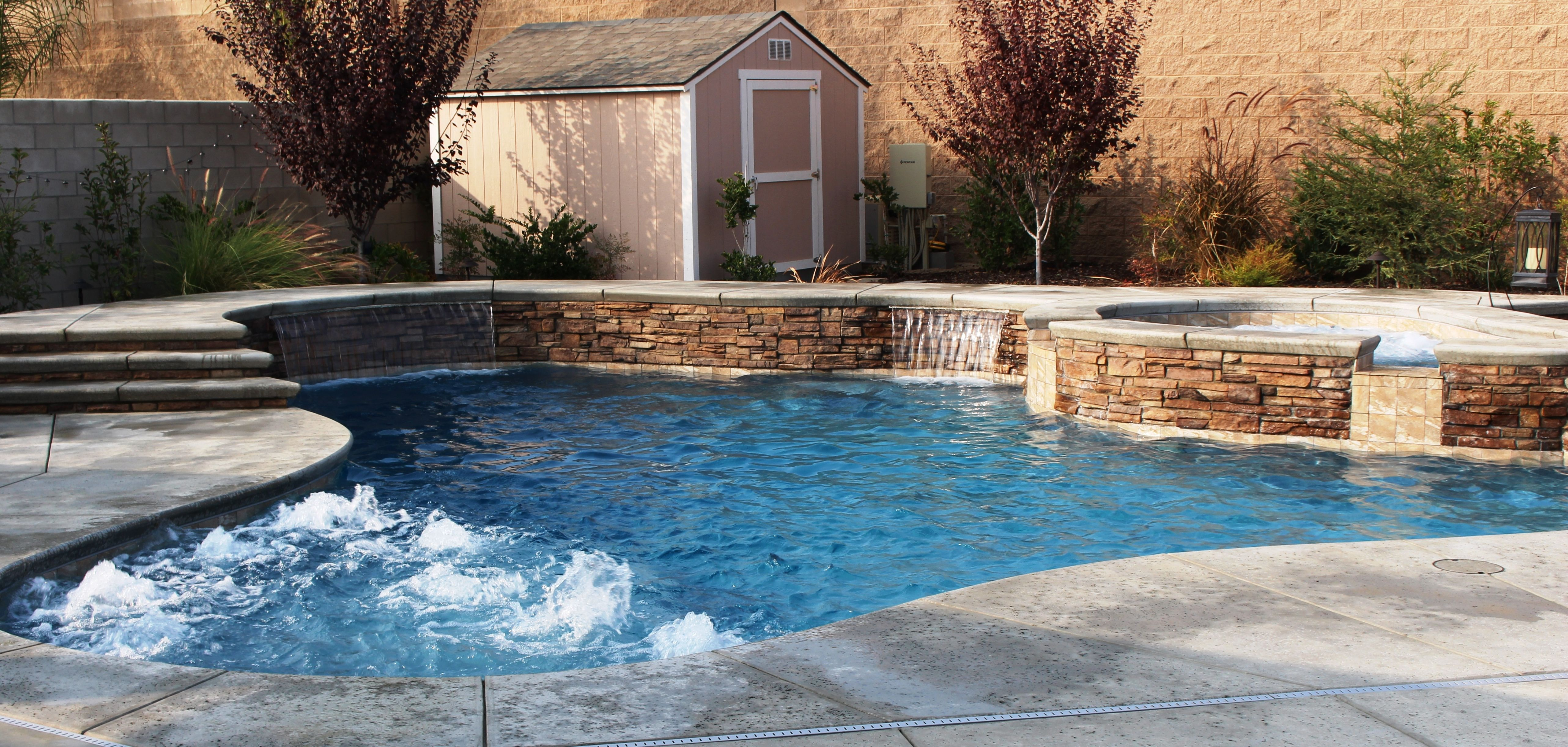Stacked stone raised wall with sheer descents & bubblers make the ...