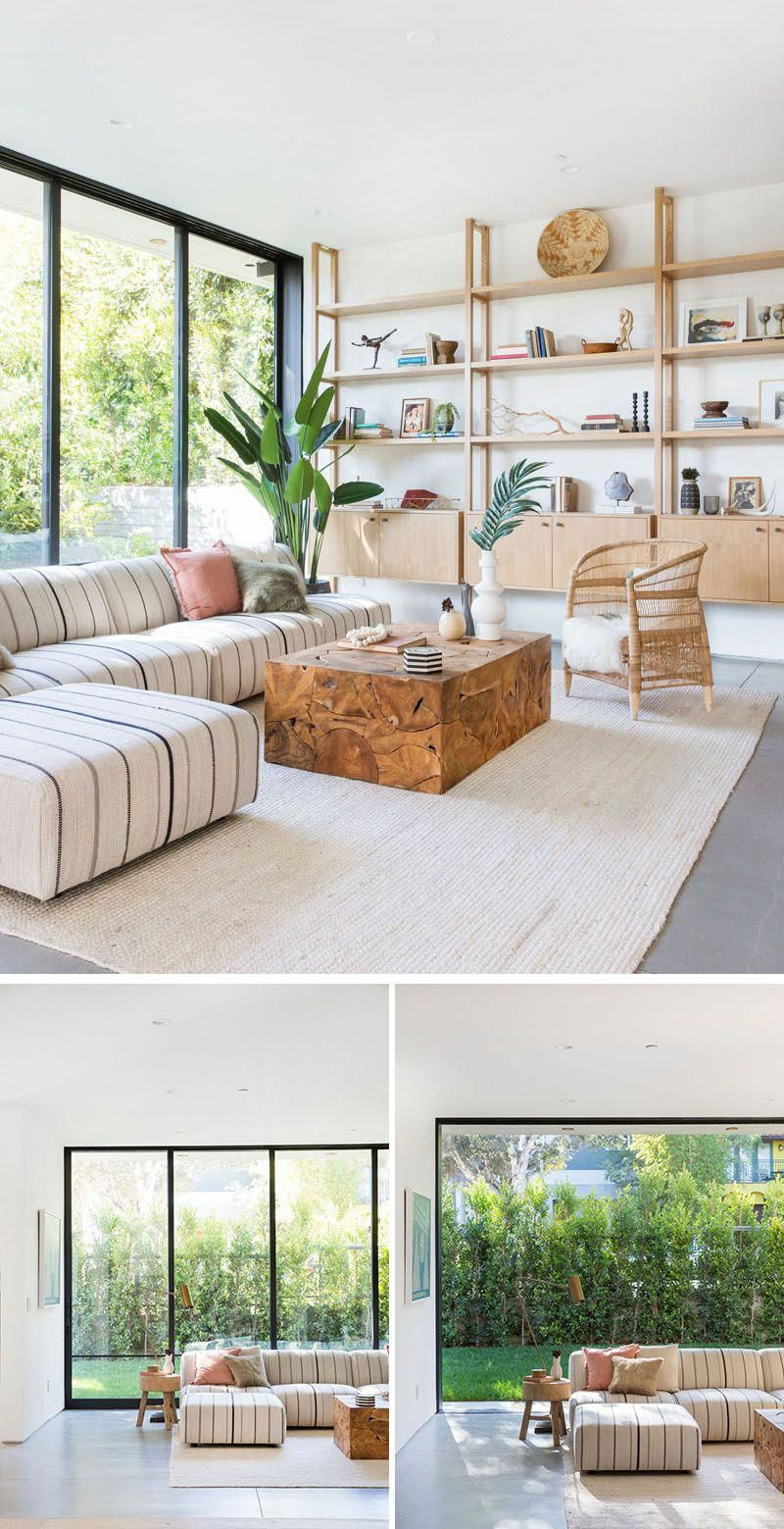 This contemporary living room features a wall of light wood shelving, while floor-to-ceiling sliding glass wall floods the interior with natural light. #LivingRoom #Shelving #SlidingGlassWall #livingroomlayout