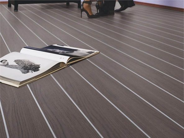 These Dark Grey Floorboards Are Separated By Shiny Aluminium Spacers For An Eye Catching Contemporary Effect Oak Laminate Flooring Grey Floorboards Oak