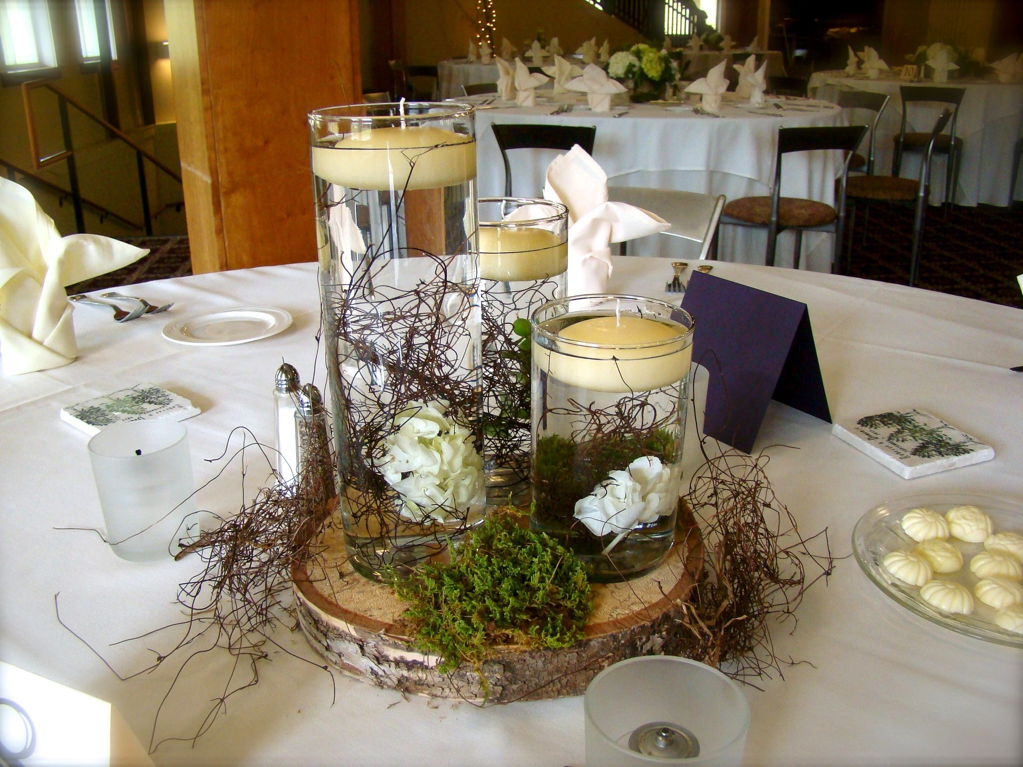 Floating candle centerpiece set on birch moss and vine